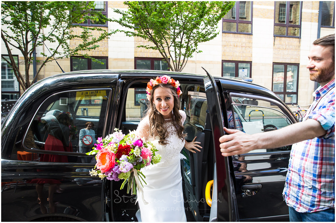 The bride steps out of a taxi outside London wedding venue