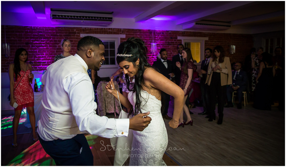 Bride and groom dance together at evening reception