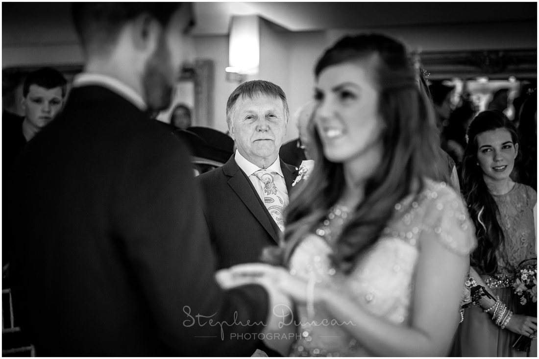The bride's father and other guests watch on as the bride and groom make their marriage vows