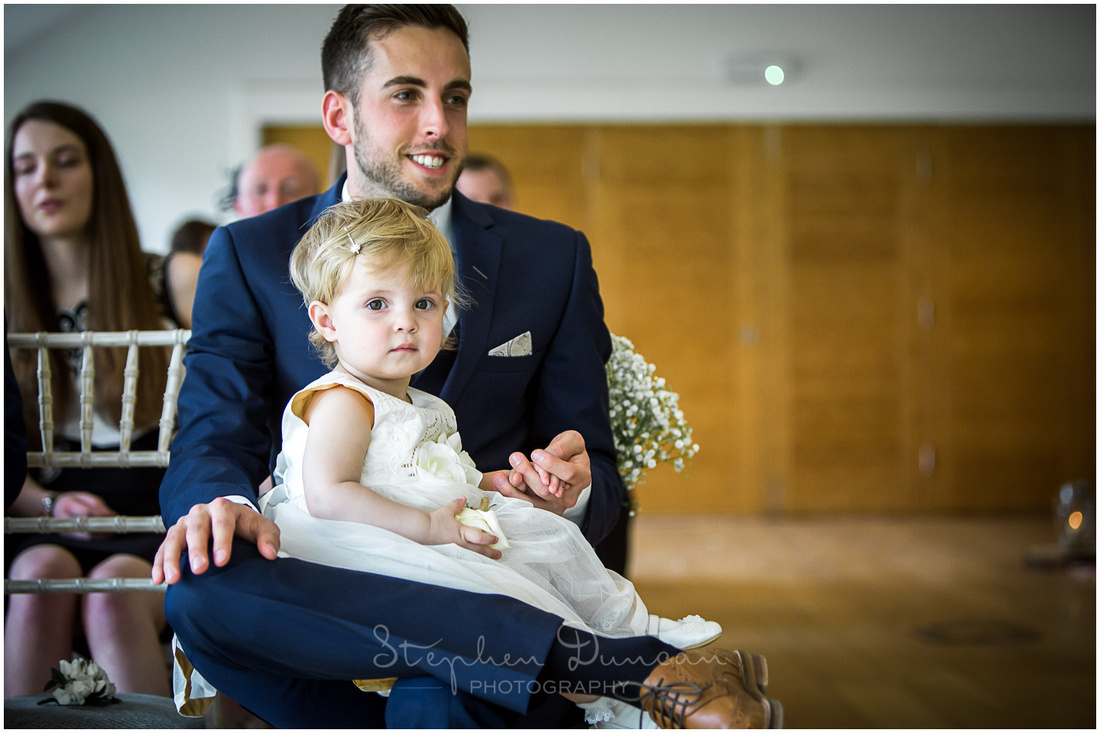The flower girl sits on the best man's lap, watching on as the register is signed