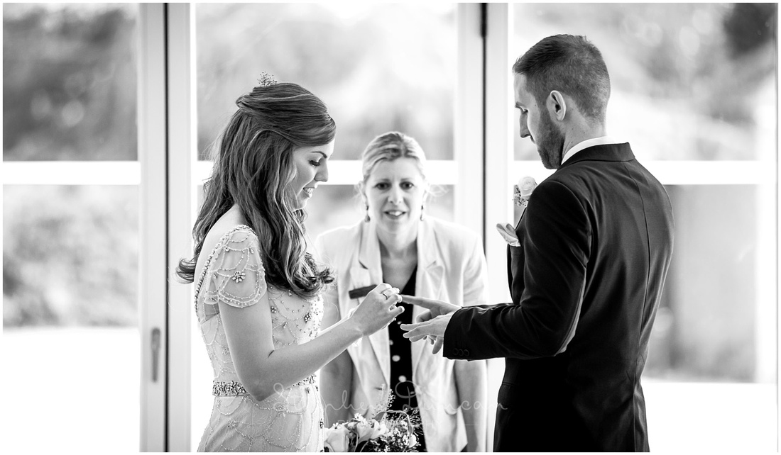 The bride and groom exchange rings as part of the marriage service in the garden room at Wasing Park
