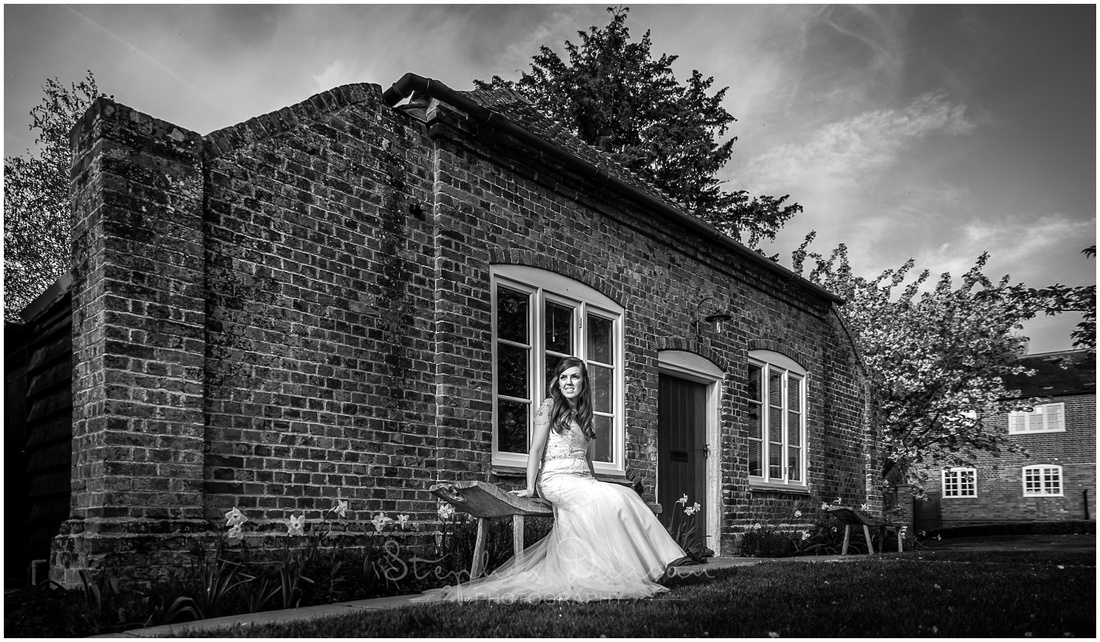 The bride poses in the gardens of Wasing Park