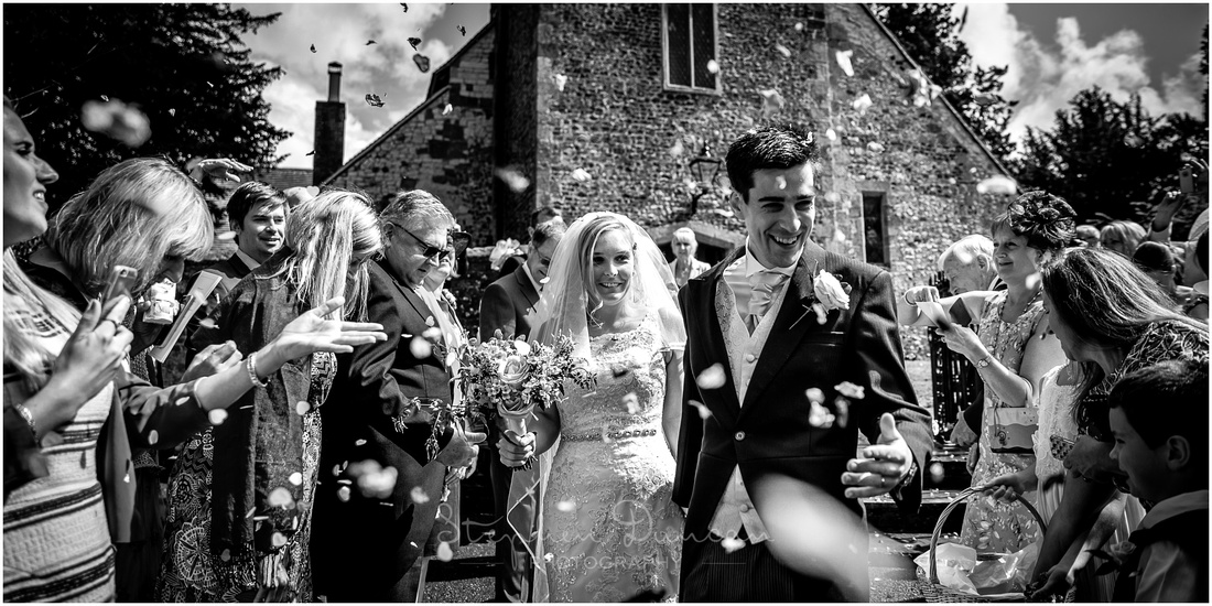 Black and white image of confetti being thrown at wedding couple outside St Mary's Church in Buriton near Petersfield, Hampshire