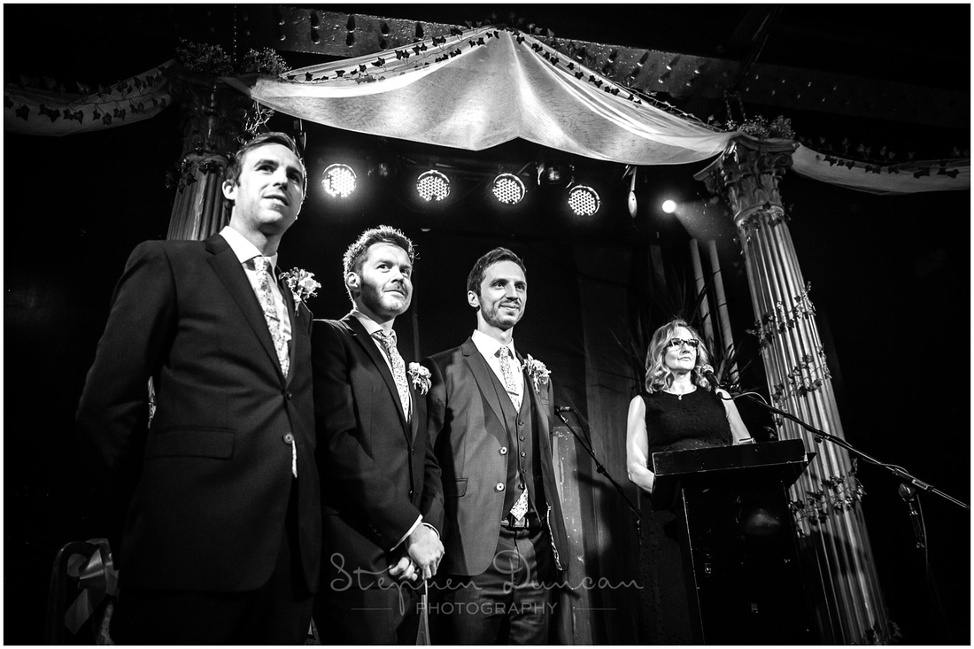 Groom with best men stood on stage in ceremony room at London wedding venue