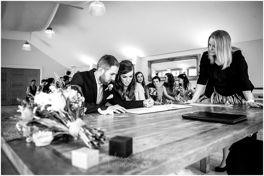 The bride and groom sign the documentation which makes the marriage legal