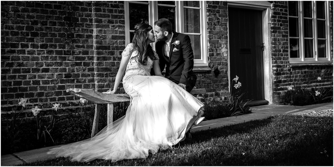 Black and white image with bride and groom sat on bench
