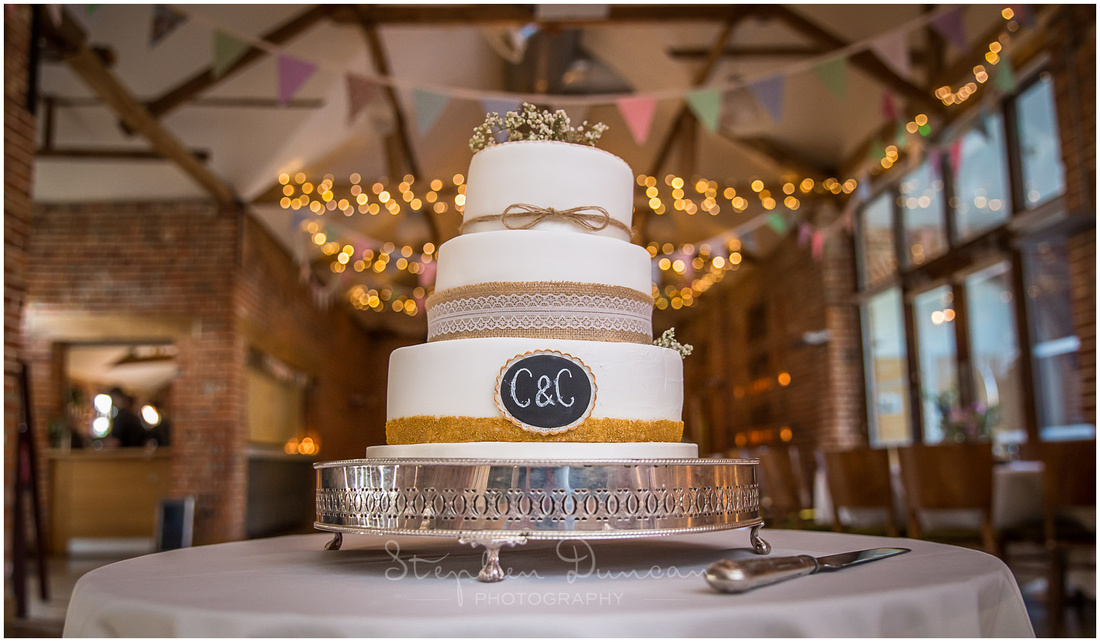 Colour photograph of wedding cake inside barn