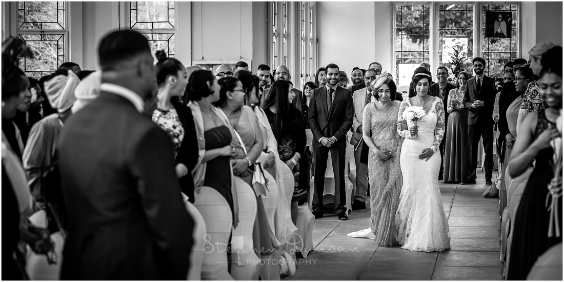 The bride and her mother walk down the aisle together to meet the groom
