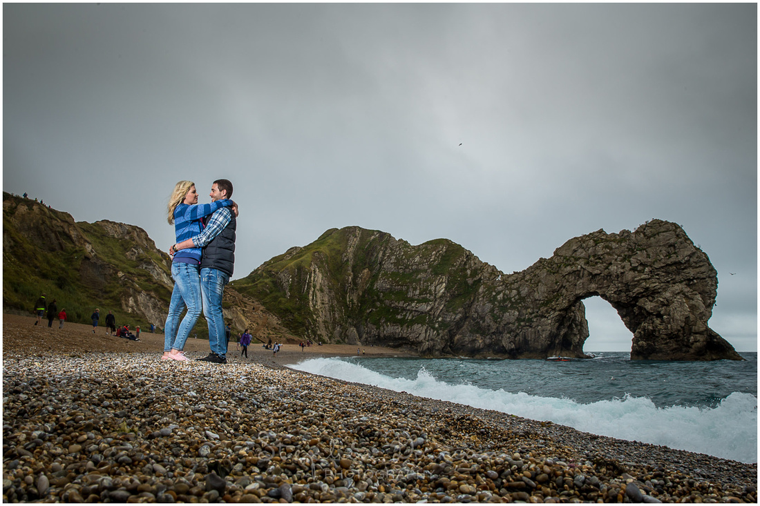 Couple facing each other with Durdle DOor landmark in background, photographed using off-camera flash for dynamic effect