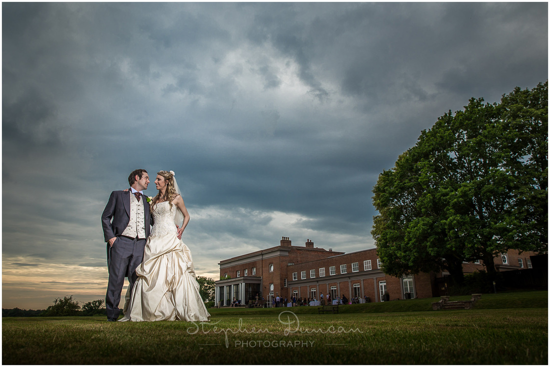Bride and groom posed with view of hotel
