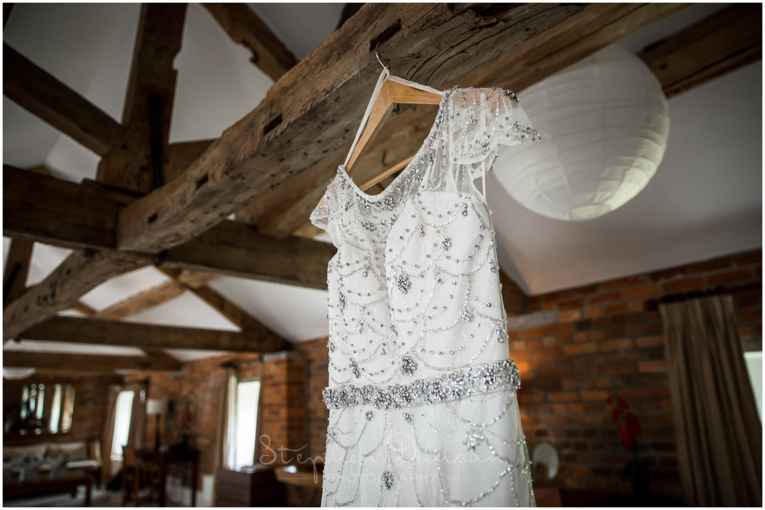 Detail of dress hanging from old beam in bridal suite