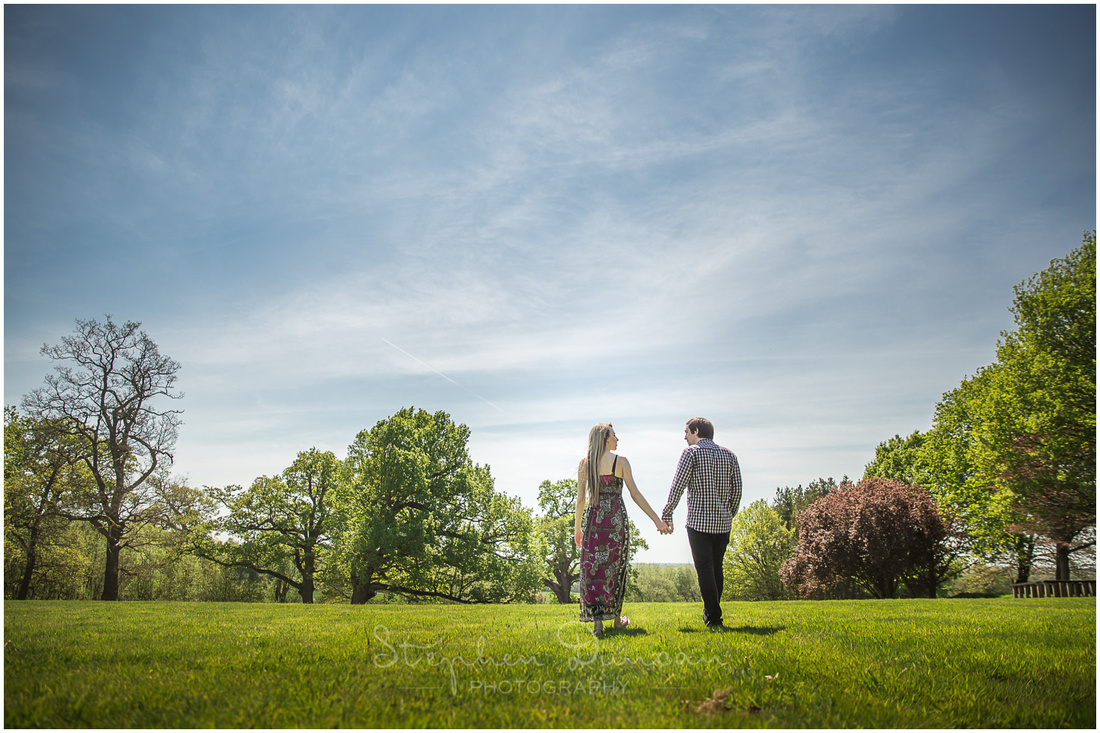 Bride and groom walking hand in hand in gardens with blue skies