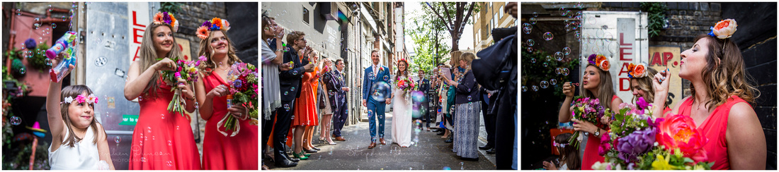 Married couple walk through bubbles after wedding