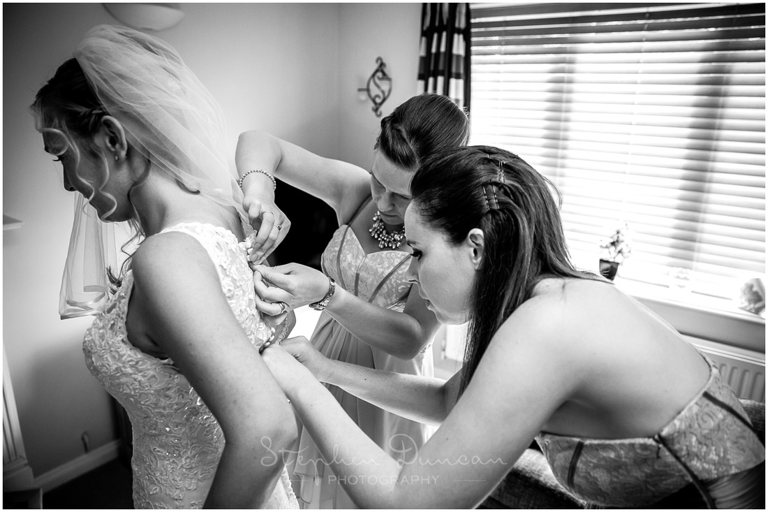 Bridesmaids button up the bride's wedding dress