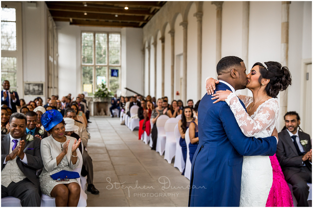 Bride and groom celebrate their marriage with the traditional kiss