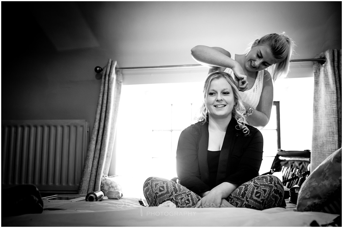 Black and white image of bride during hair and make-up