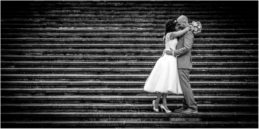 Black and white photo of couple on the steps between the Law Courts and the Great Hall in Winchester