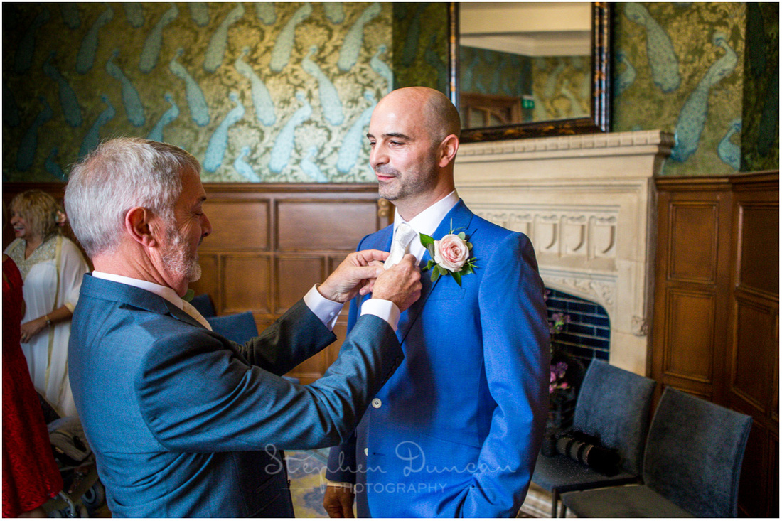 Finishing touches to the groom's tie before the bride arrives