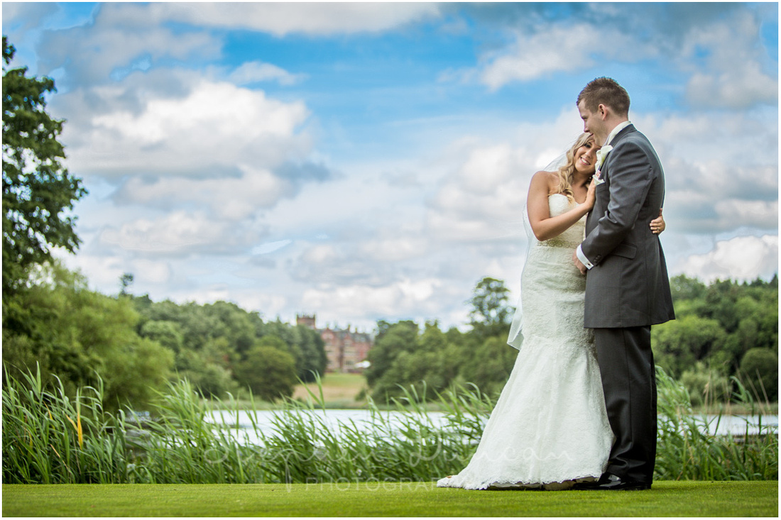 Bride and groom together by the lake, with the old college in the background
