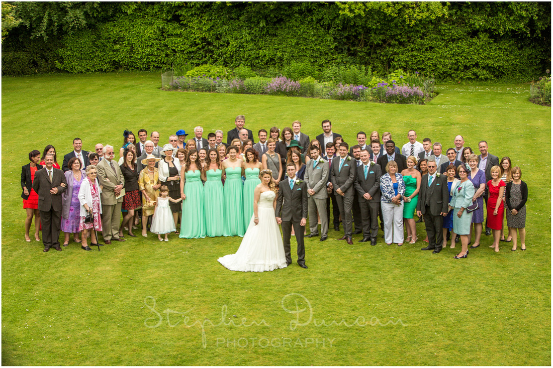 The entire wedding party gather in the gardens for a photo