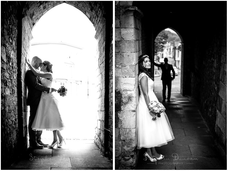 Black and white photos of bride and groom in an arched tunnel by the Westgate at the top end of Winchester