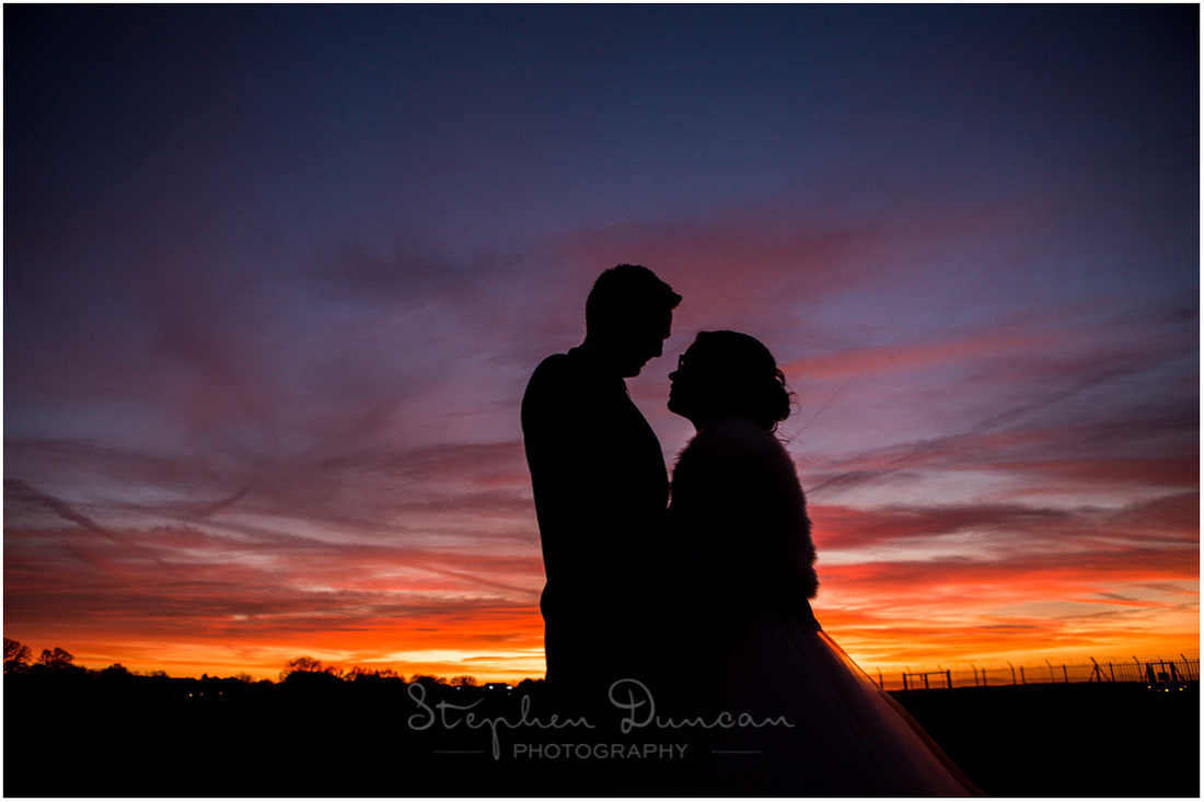 Sunset silhouette of bride and groom
