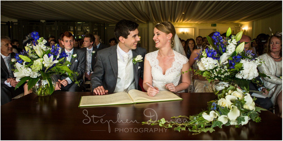 Southdowns Wedding Photography Bride and groom sign the marriage register surrounded by friends and family