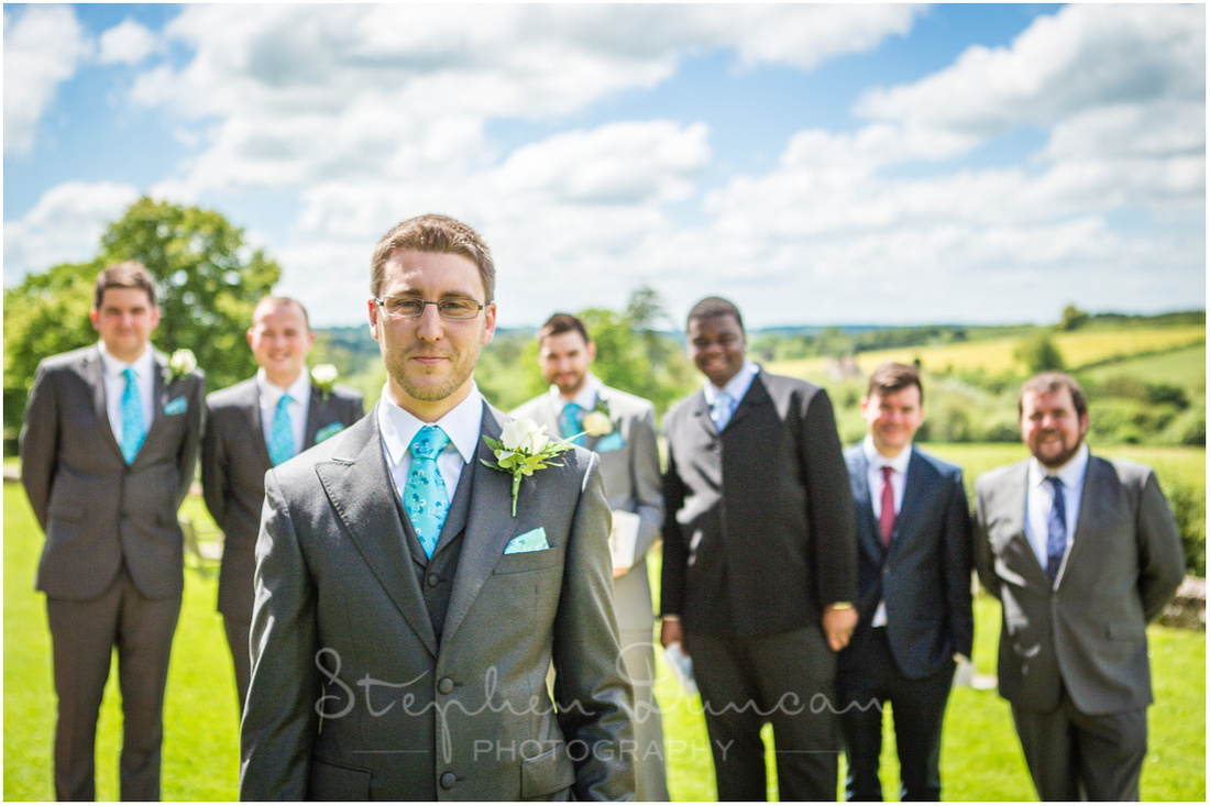 Outdoors in summer sunshine with best man and ushers in background