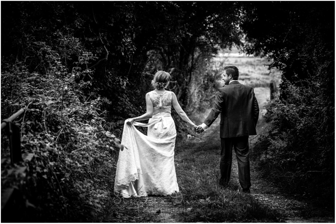 Black and white photo of couple walking along country track near Sopley Mill