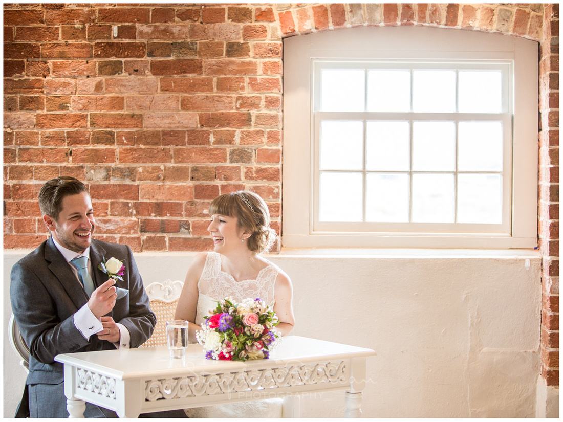Bride and groom relax at the table after making their vows and before signing the register
