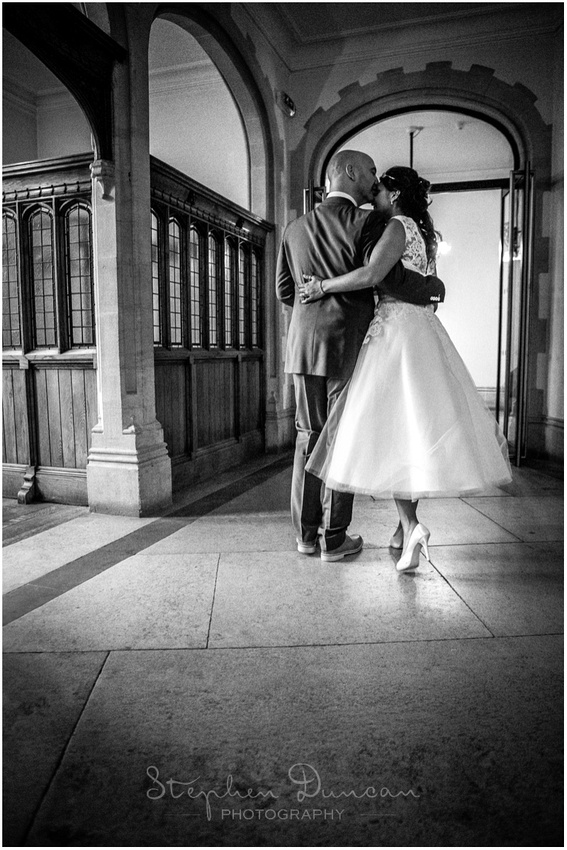 Black and white image of the bride and groom in the corridor outside the Basing Room
