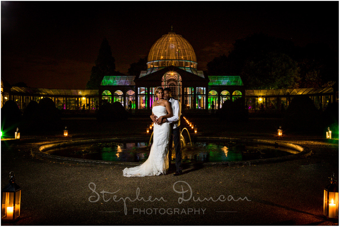 The bride and groom together by the pond at the front of the conservatory, late in the evening with dramatic lighting in the background