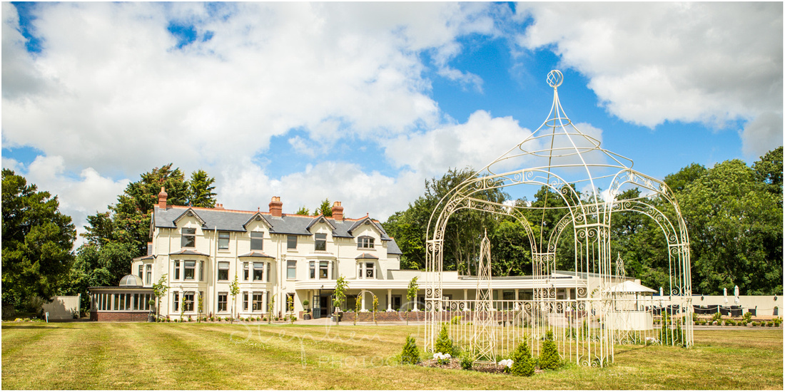 Blue skies over the lawns of the recently refurbished hotel, with gazebo in the foreground