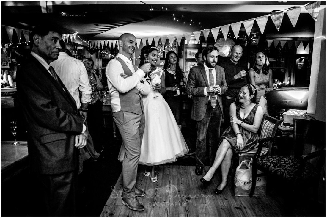 Bride, groom and guests laugh during wedding speeches