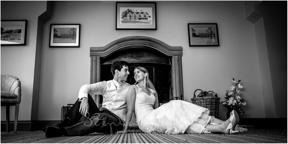 Portrait of the couple in the hotel's lounge, in front of the beautiful stone fireplace