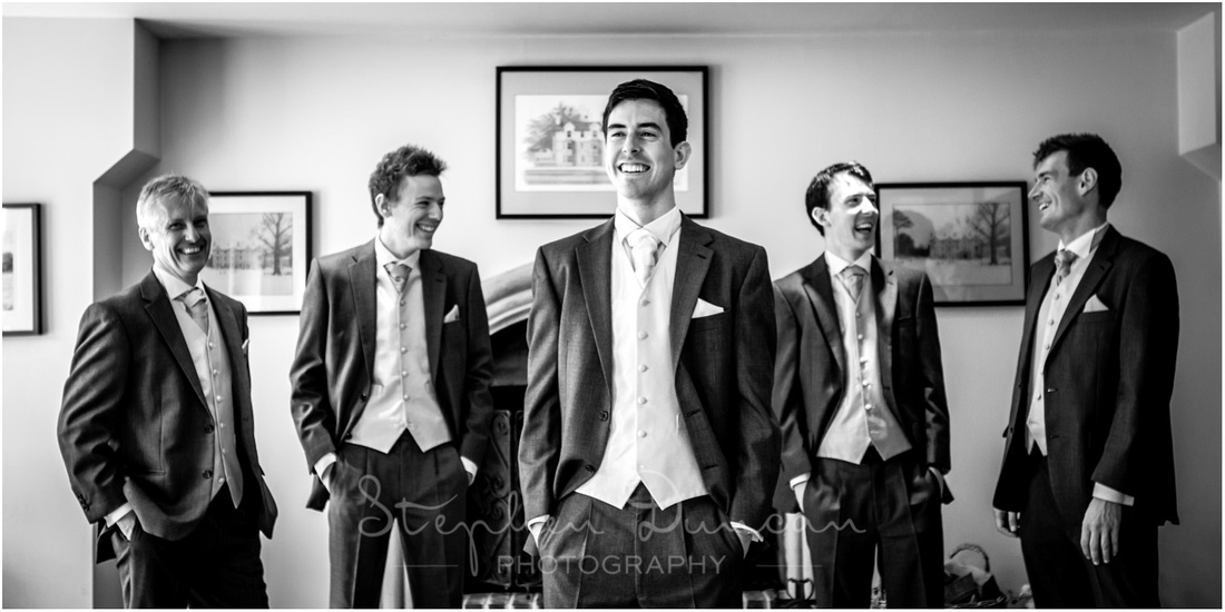 The groom with best man and ushers in front of the stone fireplace in the lounge