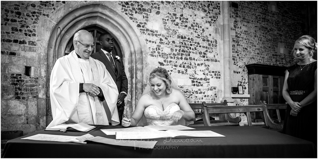 The bride sits in a side-chapel to sign the marriage register