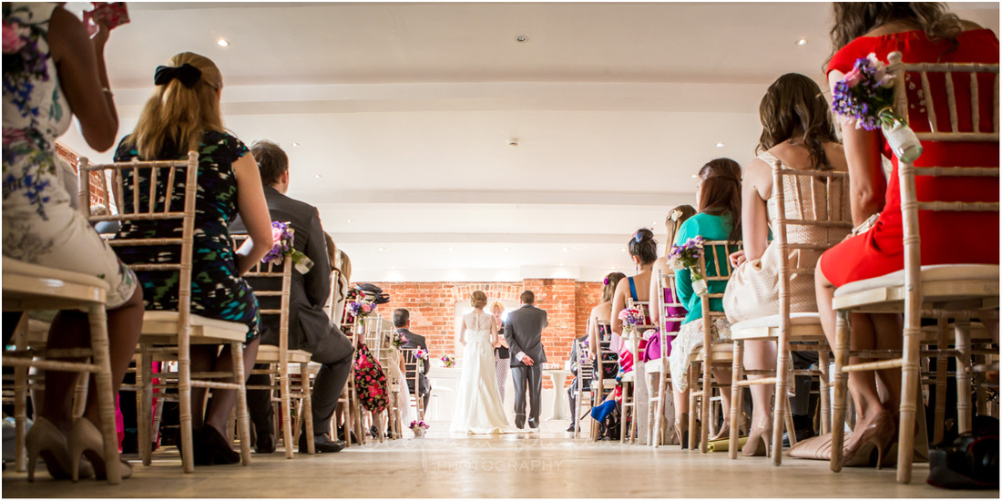 Bride and groom in sun-lit wedding ceremony room at Sopley Mill