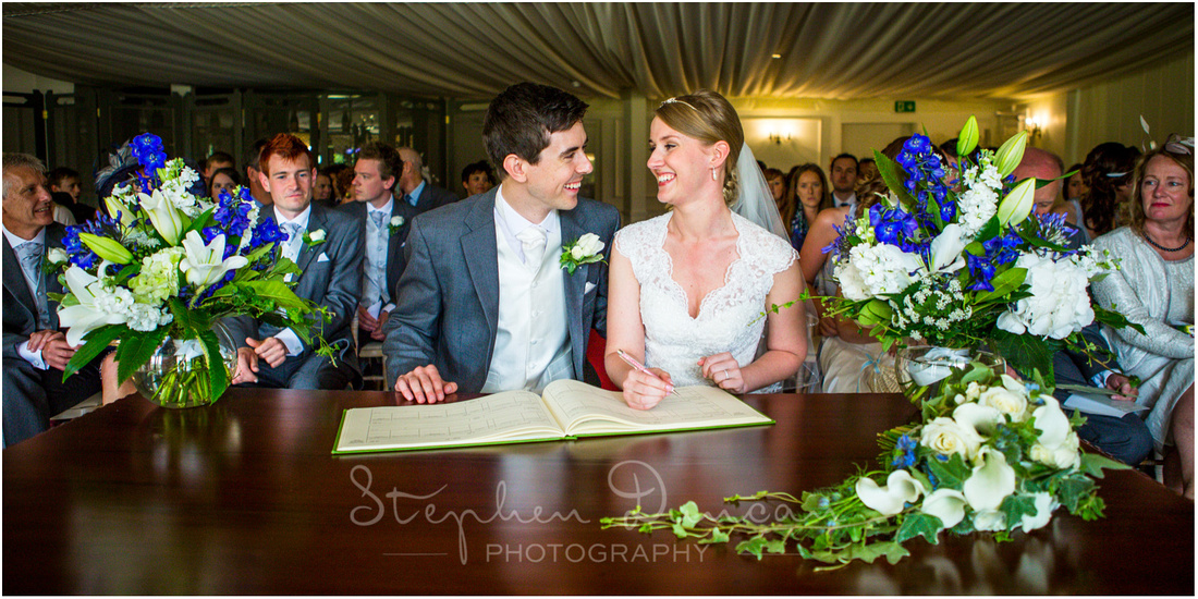 The bride and groom sign the register with guests in the background