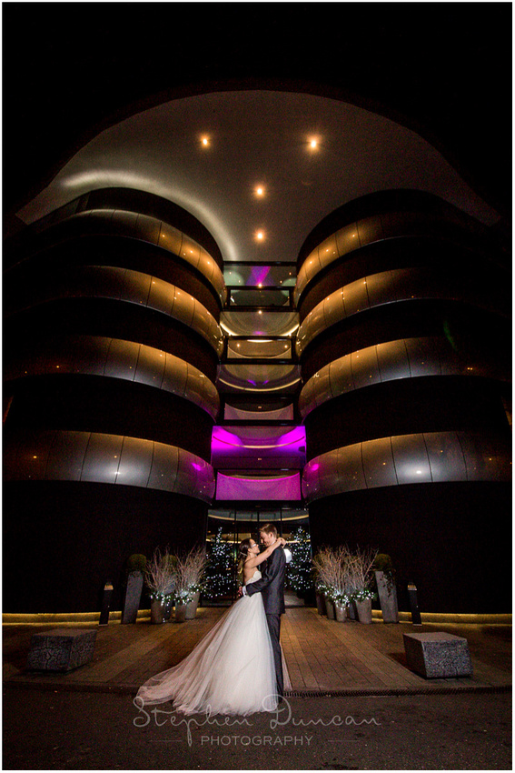 Bride and groom posed outside the main entrance to the hotel