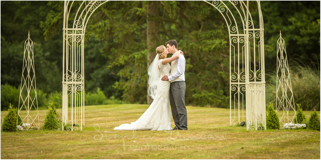 Bride and groom kissing in the gazebo on the hotel's lawn