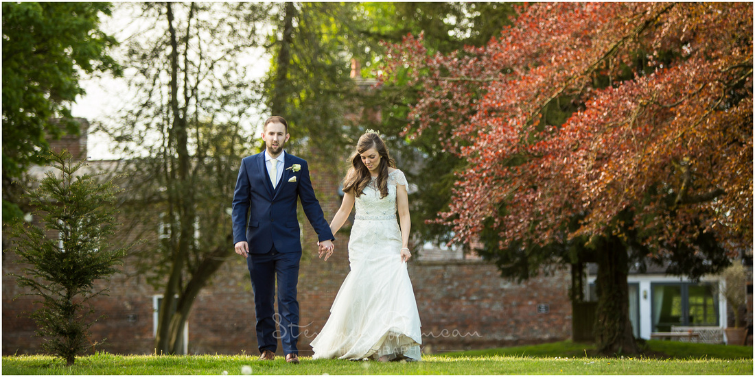 Bride and groom walk hand-in-hand across the lawn at Wasing Park wedding venue