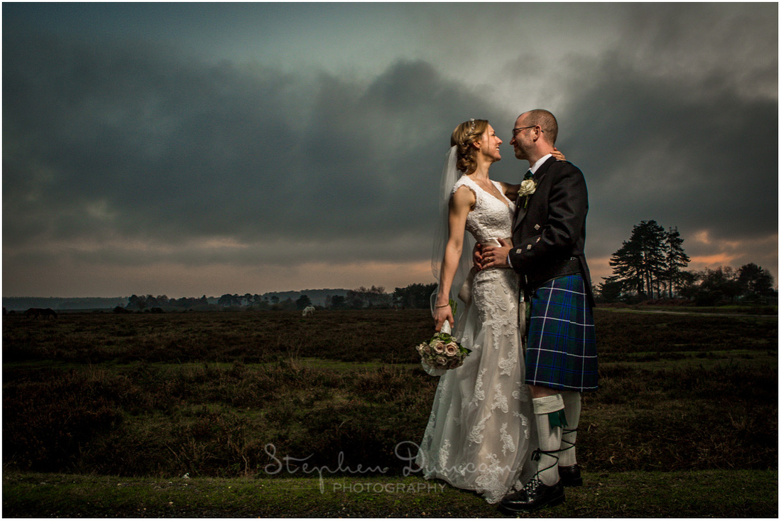 Bride and groom together on a winter's evening near Beaulieu in the New Forest
