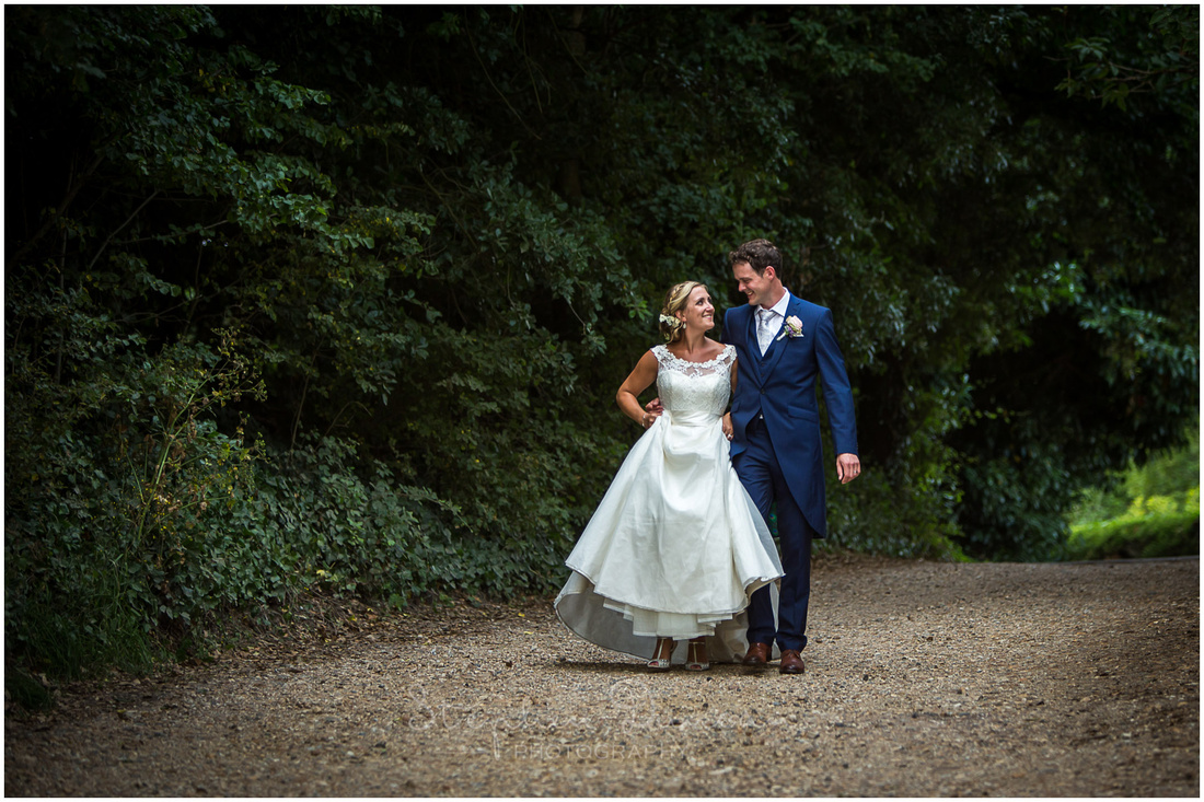 Bride and groom walk together along a stone track towards the venue