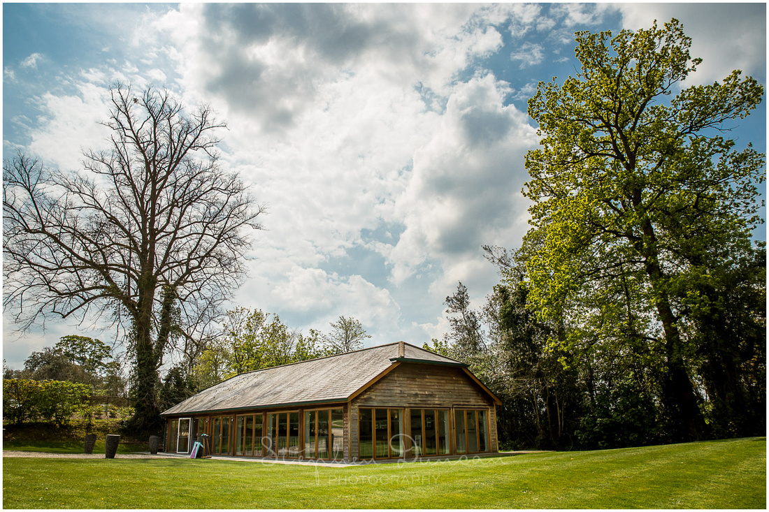 The garden room at Wasing Park wedding venue is a barn with huge class windows set across the lawn from the reception barn