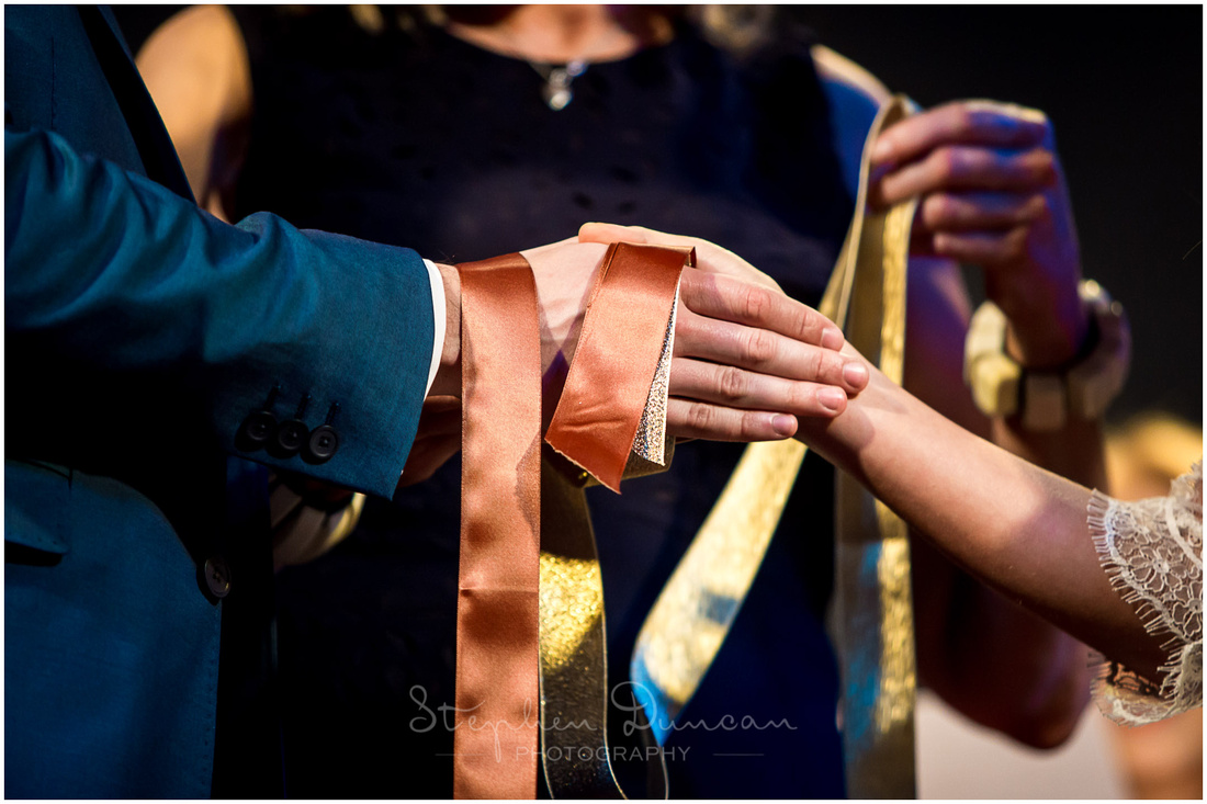 Ribbons are tied around the hands of the couple as they make their commitment to each other