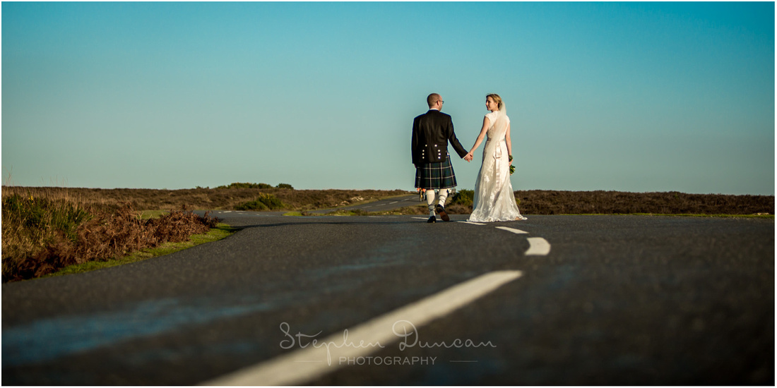 Bride looks back over her shoulder as the couple walk along a Forest road in the Winter sun