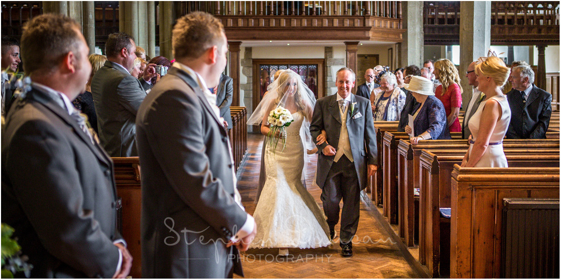 The bride walks down the aisle on her father's arm