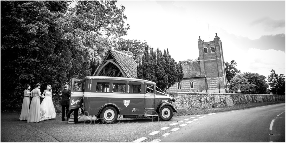 Vintage bus with bride and bridesmaids outside church