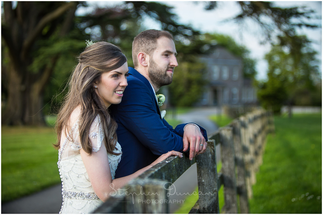 The married couple look out across the views of parkland and rolling hills, with the manor house in the background